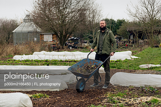 Man working in vegetable nursery, pushing wheelbarrow - p300m2166450 by FL photography