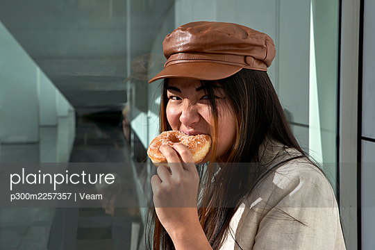Young woman eating doughnut against glass wall - p300m2257357 by Veam