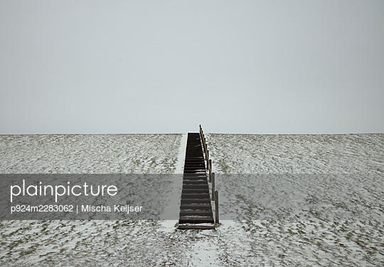 Netherlands, Friesland, Wierum, Steps in snow covered field - p924m2283062 by Mischa Keijser