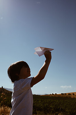 Little boy with paper plane outdoors - p1623m2289589 by Donatella Loi