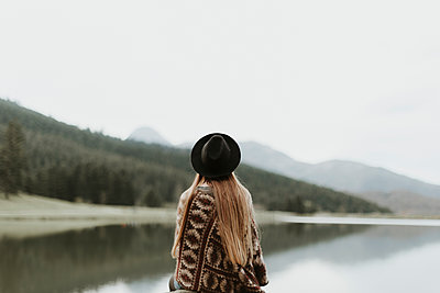 Back view of young woman wearing hat and poncho sitting in front of a lake - p300m1550194 by Oriol Castelló Arroyo