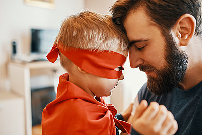 Little boy dressed up as a superhero head to head with his father - p300m1580960 by Zeljko Dangubic