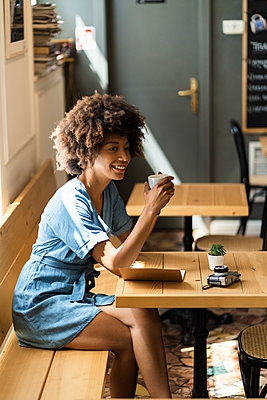 Thoughtful woman holding coffee mug while sitting at table in cafe - p300m2202642 by Giorgio Fochesato