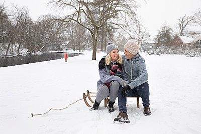 Couple sitting on sled during winter - p300m2281803 by Frank van Delft