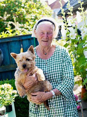Portrait of senior woman holding dog in garden - p31227450f by Peter Carlsson