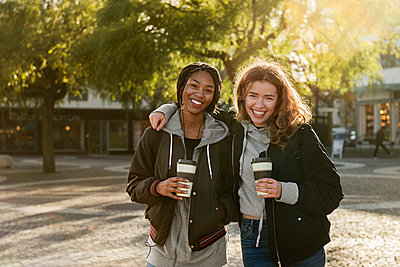 Smiling teenage girls with coffee cups - p352m2121109 by Folio Images