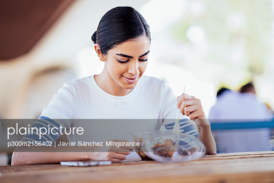 Young woman sitting at table eating takeaway food - p300m2156402 by Javier Sánchez Mingorance