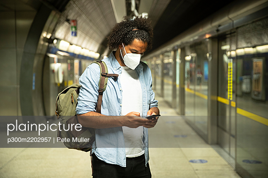 Young man wearing protective mask standing at underground station platform, London, UK - p300m2202957 by Pete Muller