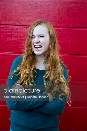 Portrait of angry teenage girl with crossed arms in front of red wooden wall