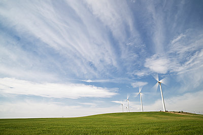 Wind turbines on field against cloudy sky - p1166m1473639 by Cavan Images