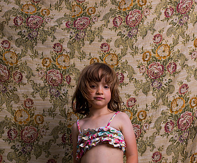Girl wearing bikini top against floral wallpaper - p1279m1424488 by Ulrike Piringer