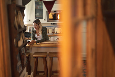 Pregnant woman texting on the phone in kitchen - p1315m2041019 by Wavebreak