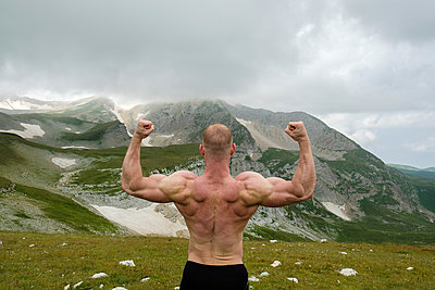 Man athlete posing on background of the Caucasus Mountains - p1363m2063249 by Valery Skurydin