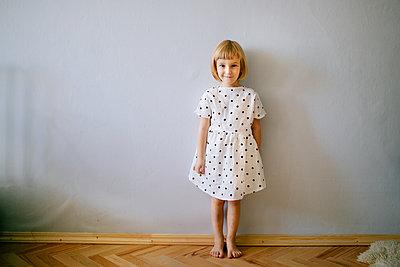 Blondes Mädchen in gepunktetem Kleid steht an einer Wand - p1414m2044861 von Dasha Pears