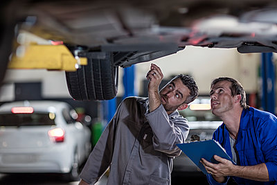Two car mechanics in a workshop examining car together - p300m1189176 by zerocreatives