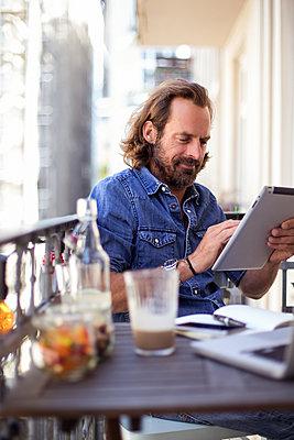 Mann arbeitet mit Tablet auf dem Balkon - p788m1424710 von Lisa Krechting