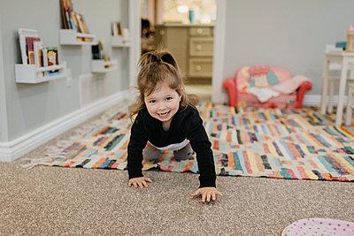 A young girl crawling towards the camera and smiling. - p924m2186227 by Sara Monika