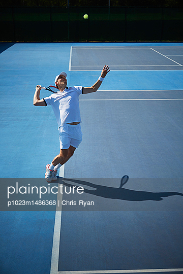 Young male tennis player playing tennis, serving the ball on sunny blue tennis court