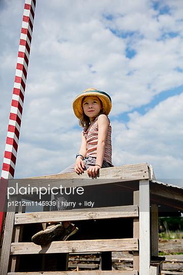 Mädchen mit Strohhut auf einer Bretterbude - p1212m1145939 von harry + lidy