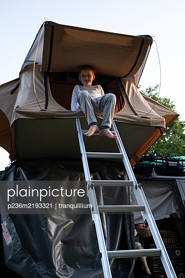 Boy in tent on rooftoop of mobile home - p236m2193321 by tranquillium