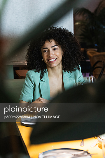 Barcelona, Spain. Smiling female friends dining in restaurant. 20-30 years, birthday, celebration, restaurant, multicultural, three people, party, friendship, dining table, multiracial group, togetherness, fun, meals, drink, people, smartphone, happy - p300m2286894 von NOVELLIMAGE