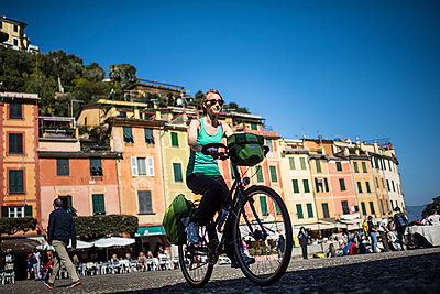 Young woman on a bicycle in Portofino - p1007m1540357 by Tilby Vattard
