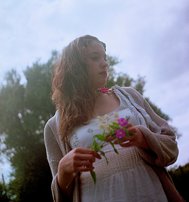 Woman holding flowers  against a dramatic sky - p1072m829540 by Tracy Jean Shields