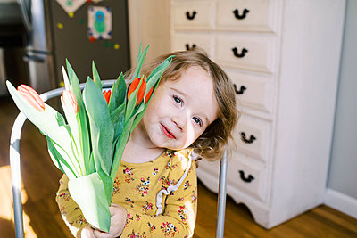 Little two year old girl holding a bunch of tulips. - p1166m2162811 by Cavan Images