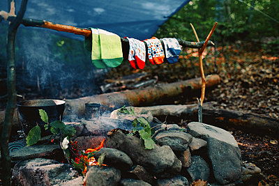 Drying wet socks on the bonfire during camping. Socks drying on fire. Active rest in forest. - p1166m2193928 by Cavan Images