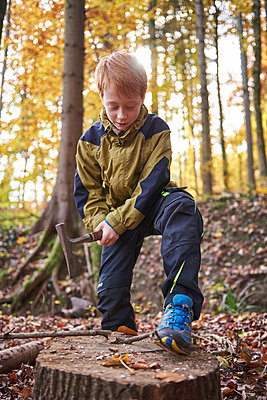 Redheaded boy treating branch with bow in autumnal forest - p300m1417033 by Jess Derboven