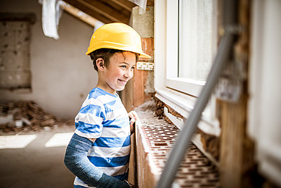 Boy wearing hardhat looking through window at construction site - p300m2287506 by Epiximages