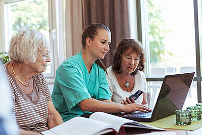 Nurse with senior women buying medicine online using laptop and credit card at nursing home - p426m2072585 by Kentaroo Tryman