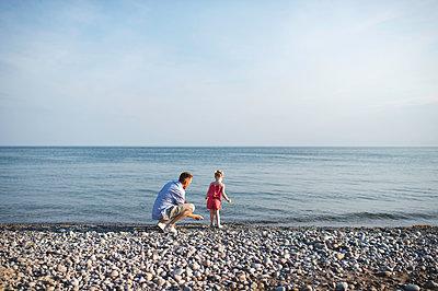 Mid adult man and daughter skimming stones at Lake Ontario, Oshawa, Canada - p429m1175148 by Erin Lester