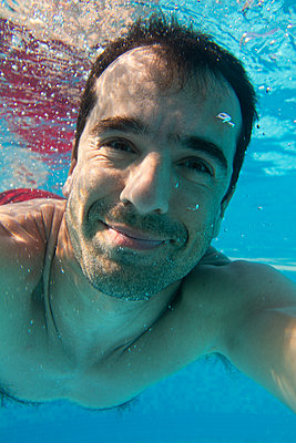 A man swimming underwater, smiling at a camera, an underwater selfie.  - p429m2200746 by Goncalo Barriga