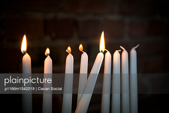plainpicture | Photo library for authentic images - plainpicture p1166m1542219 - Close-up of lit candles in ... - plainpicture/Cavan Images/Cavan Social