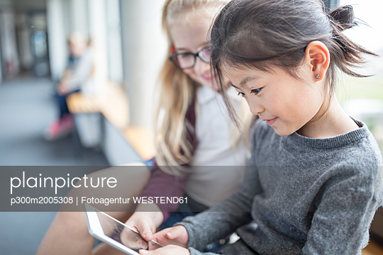 Schoolgirls sharing a tablet on school corridor - p300m2005308 by Fotoagentur WESTEND61