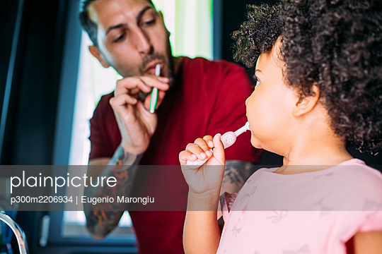 Close-up of baby girl with father brushing teeth in bathroom at home - p300m2206934 by Eugenio Marongiu