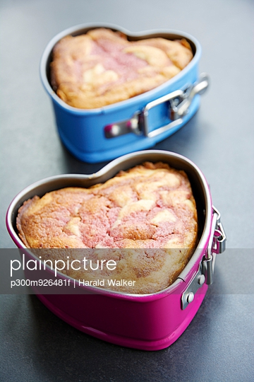 Two heart-shaped cake pans of strawberry pound cake on grey ground - p300m926481f by Harald Walker