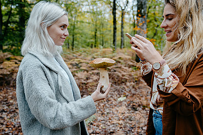 Two young women taking snapshot of a mushroom in a forest - p1166m2153971 by Cavan Images