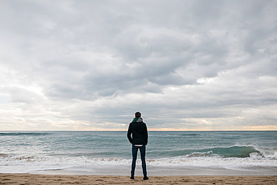 Back view of man standing on the beach in winter looking at distance - p300m1550229 by Josep Rovirosa