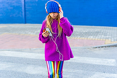 Girl wearing blue cap and oversized pink pullover listening music with headphones and smartphone - p300m2102750 von Eloisa Ramos