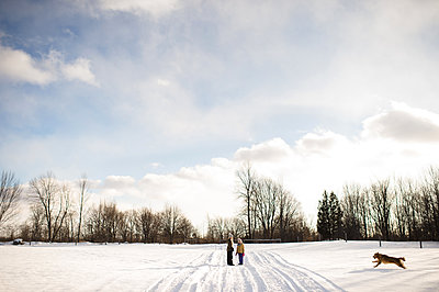 Children on snow-covered path, calling their golden retriever, Lakefield, Ontario, Canada - p429m1408114 by Erin Lester