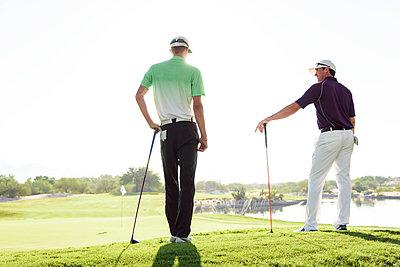 Friends talking on golf course - p555m1472898 by Kolostock