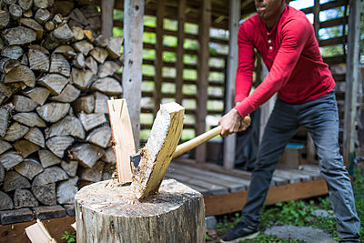 Strong Indian man splitting firewood with sharp axe. - p1166m2136685 by Cavan Images