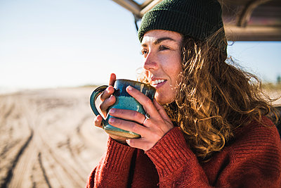 Young woman enjoying cup of coffee in the morning beach car camping - p1166m2285568 by Cavan Images