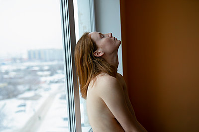 Topless woman at the window, view of the city - p1646m2253827 by Slava Chistyakov