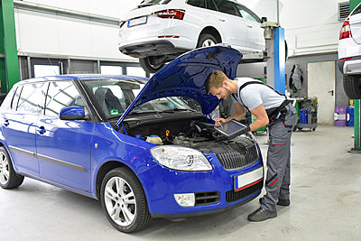 Car mechanic in a workshop using diagnostics computer at car - p300m1449441 by lyzs