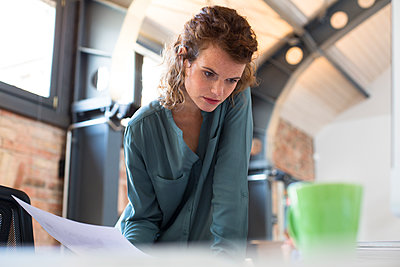 Young woman working at desk in modern office - p300m1469934 by Florian Küttler