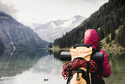 Austria, Tyrol, Alps, hiker standing at mountain lake - p300m1505315 by Uwe Umstätter