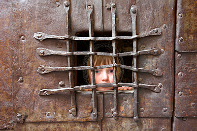 Italy, South Tyrol, Potrait of a girl behind bars - p300m980448f by Gerald Nowak